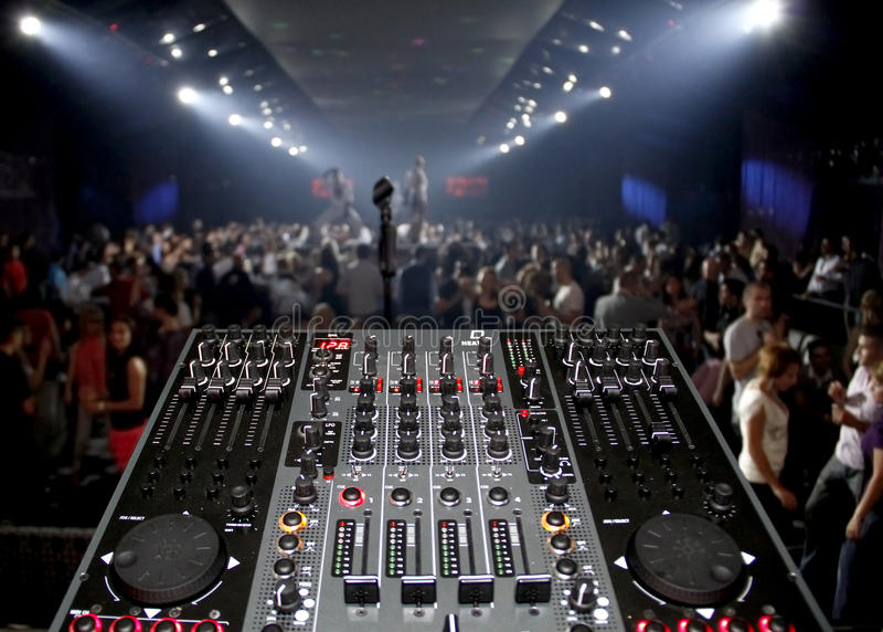 DJ desk in a nightclub party with lightshow. DJ sound mixer is pictured in a rave party