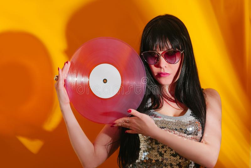 Dj disco girl party retro vintage yellow orange young woman vinyl glamour light sun sunlight set sunrise summer morning. Young DJ woman with pink vinyl enjoys stock image