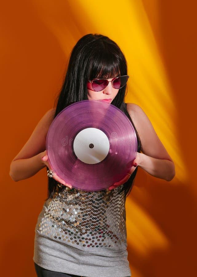 Dj disco girl party retro vintage yellow orange young woman vinyl glamour light sun sunlight set sunrise summer morning. Young DJ woman with pink vinyl enjoys royalty free stock images