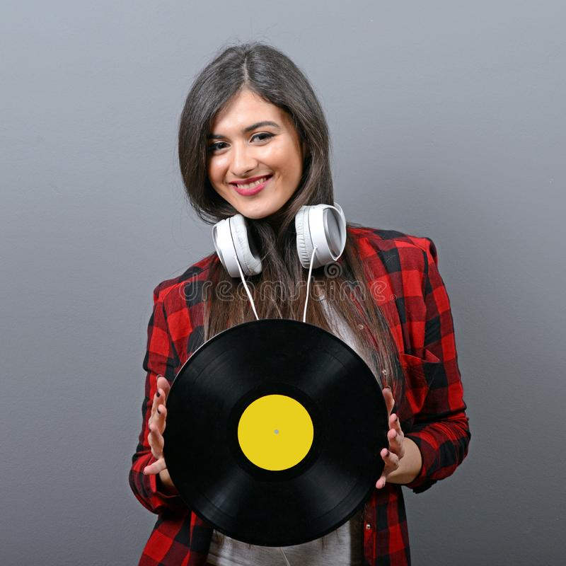 DJ fêmea bonito com fones de ouvido e vinil contra o fundo cinzento imagens de stock