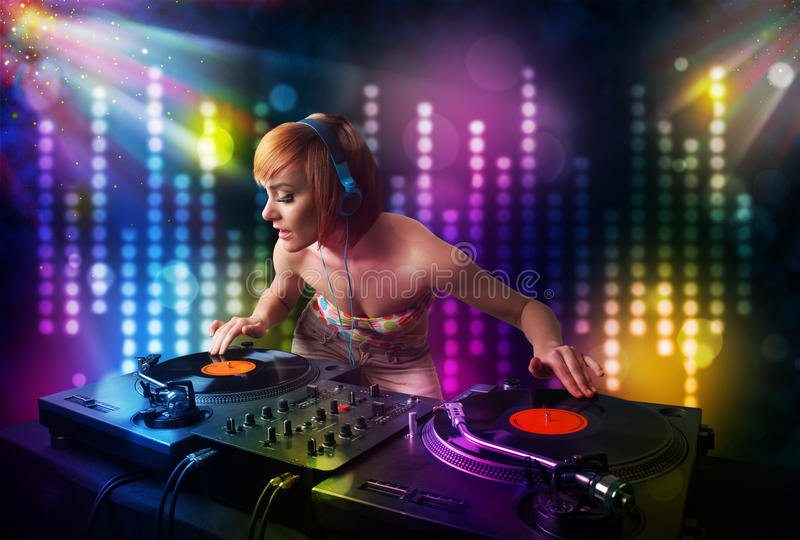 Dj girl playing songs in a disco with light show royalty free stock photo