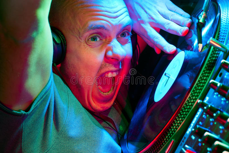 DJ going crazy on the turntables. DJ going crazy with arm in the air getting the crowd to go wild royalty free stock photo