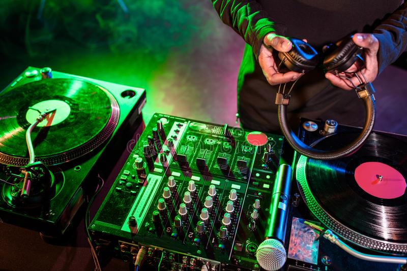 DJ with headphones over sound mixer stock photo