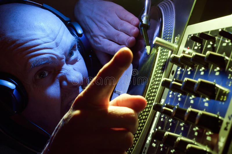 DJ with headphones pointing to crowd royalty free stock images