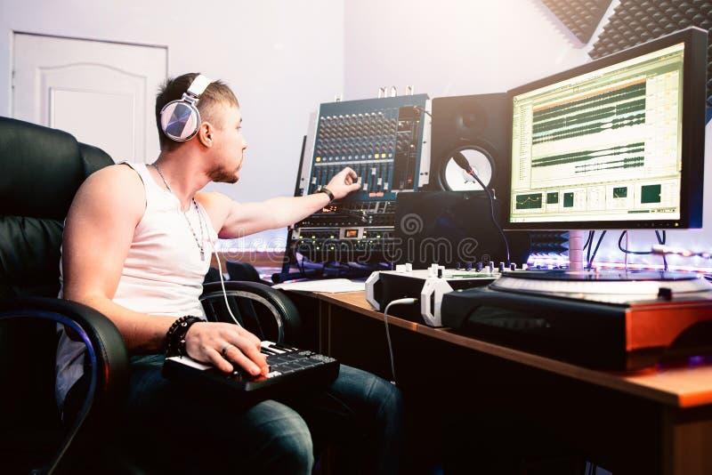 DJ justiert Ausrüstung im soliden Tonstudio stockfotos