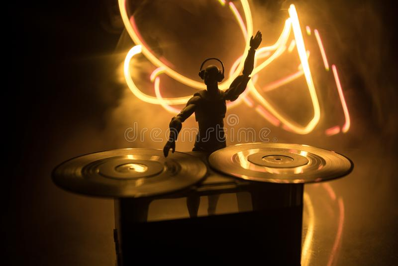 Dj-klubbabegrepp discjockey som blandar och skrapar i en nattklubb Mankontur på vinylskivtallrik, strobeljus och dimma på bakgrun royaltyfri bild