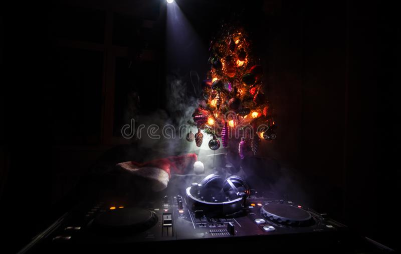 DJ-Mischer mit Kopfhörern auf dunklem Nachtklubhintergrund mit Weihnachtsbaum Sylvesterabend Schließen Sie herauf Ansicht von neu lizenzfreies stockbild
