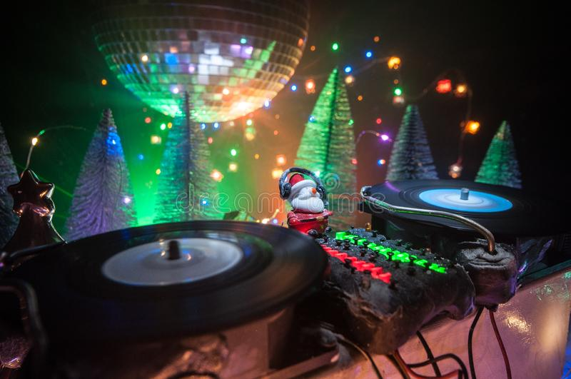 Dj mixer with headphones on dark nightclub background with Christmas tree New Year Eve. Close up view of New Year elements on a Dj royalty free stock photo