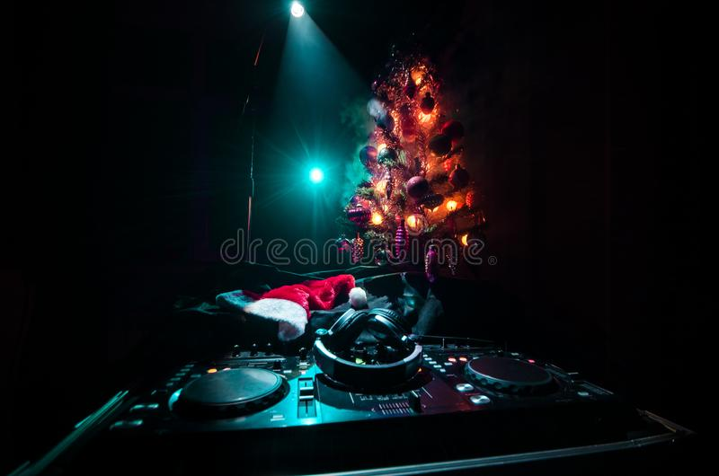 Dj mixer with headphones on dark nightclub background with Christmas tree New Year Eve. Close up view of New Year elements or symb stock photography