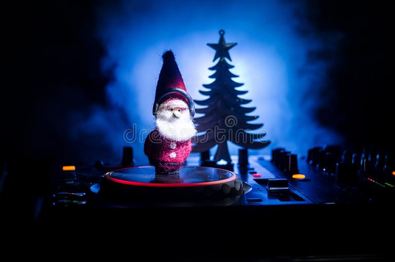 Dj mixer with headphones on dark nightclub background with Christmas tree New Year Eve. Close up view of New Year elements or symb. Ols (Santa Clause, Snowman royalty free stock images
