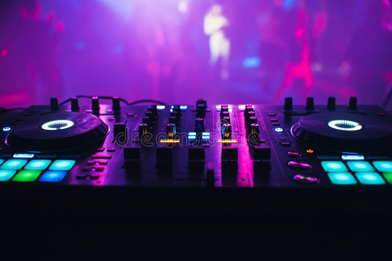 DJ mixer on the table background the night club. And dancing people royalty free stock photo