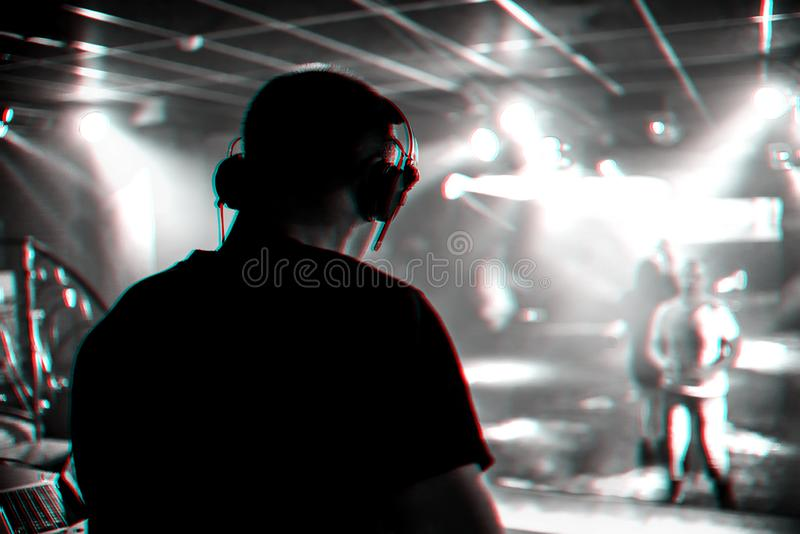 DJ mixes music in a nightclub with people dancing. On the dance floor. Black and white photo with glitch effect and small grain royalty free stock photography