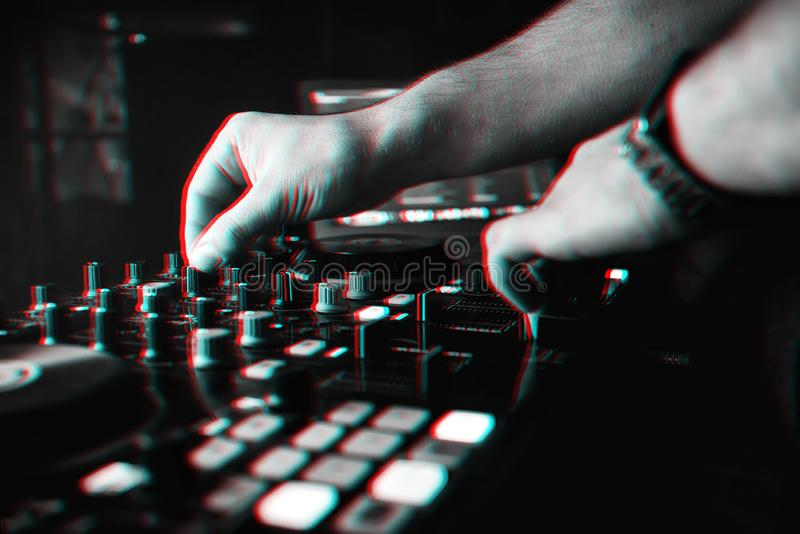 DJ mixes the track in nightclub at party hands. Driving controllers. Black and white photo with glitch effect and small grain royalty free stock images