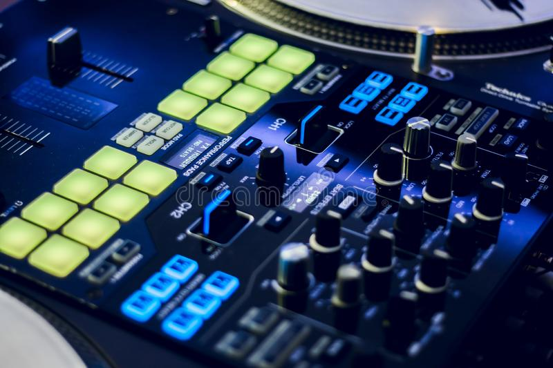 DJ mixing deck and turntables at night with controls for mixing music for a party or disco royalty free stock images