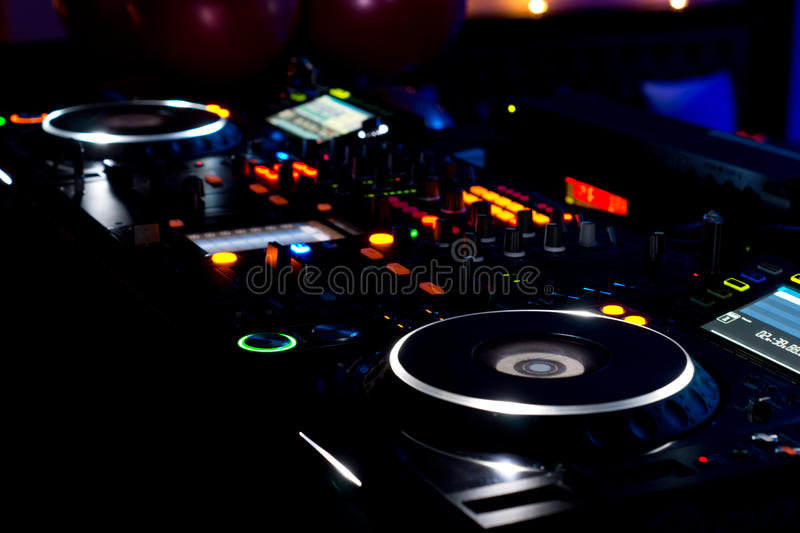 DJ music deck, turntables and equipment. Close up view at night of the colourful lights on a DJ music deck, turntables and audio mixing equipment at a royalty free stock image