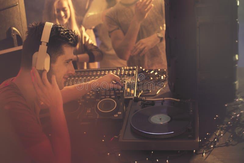 DJ obsiadanie obok turntable obrazy stock