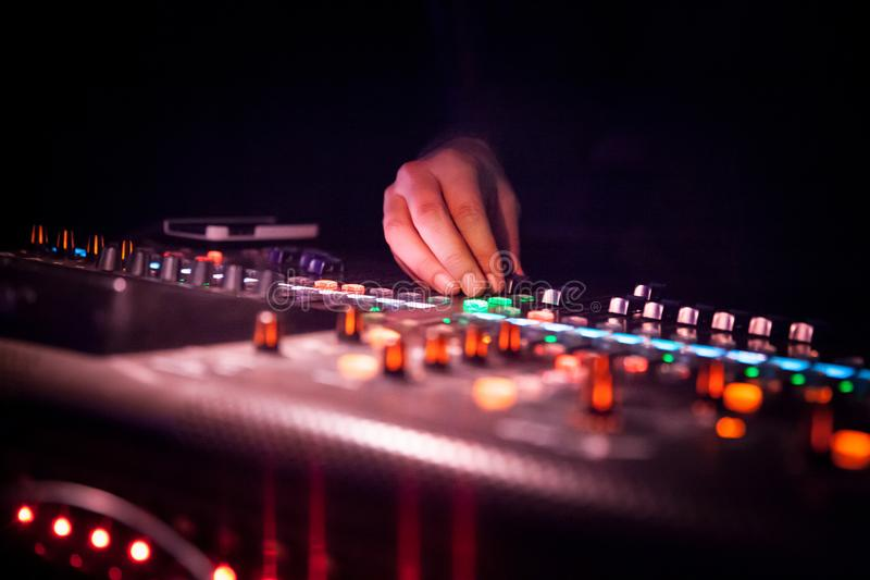 DJ operating soundboard or mixing console use in sound recording and reproduction. DJ operating a sound recording and reproduction, and sound reinforcement royalty free stock image