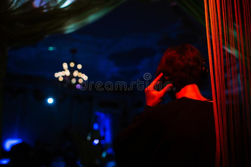 DJ at the party is illuminated with red light royalty free stock photo