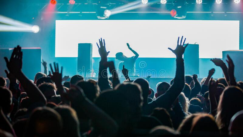 DJ performing for a crowd of party people with their hands in the air stock images