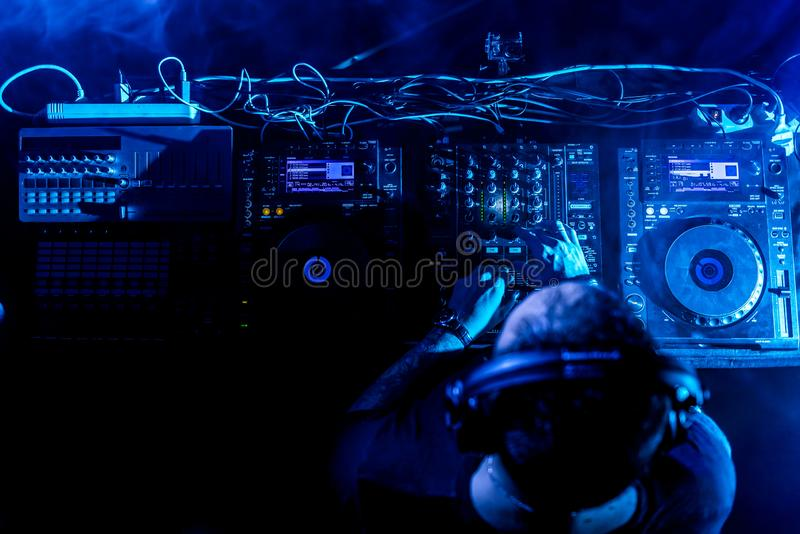 DJ Playing House and Techno Music in a Night Club. Mixing and Controlling the Music. DJ Mixing House and Techno Music in a Club. Controlling the Music royalty free stock photos