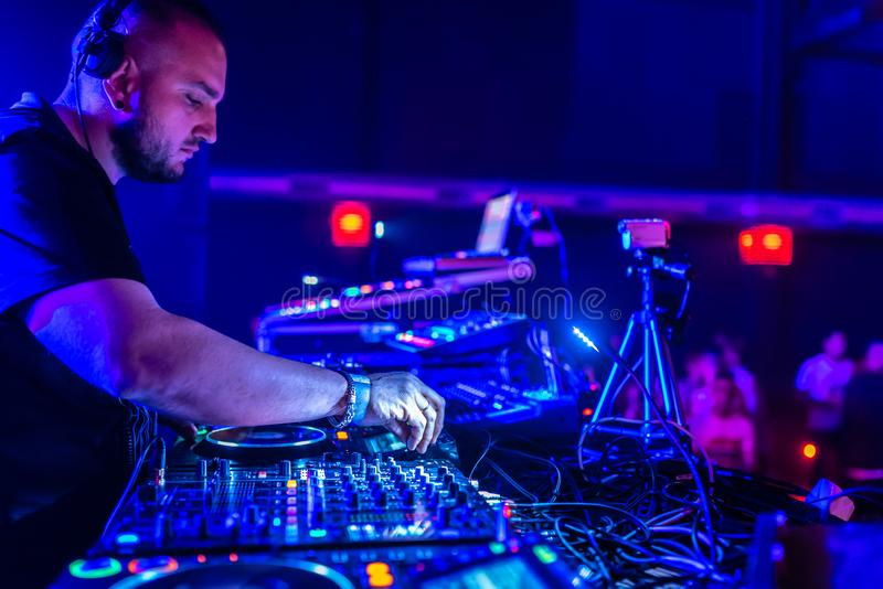 DJ Playing House and Techno Music in a Night Club. Mixing and Controlling the Music. DJ Mixing House and Techno Music in a Night Club. DJ Controlling the Music stock images