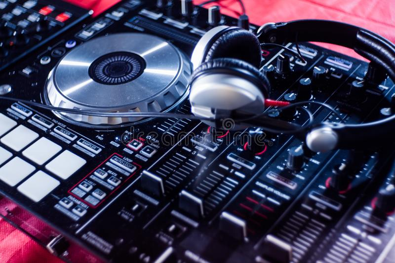 DJ playing music at mixer closeup and mixes the track in the nightclub royalty free stock photo