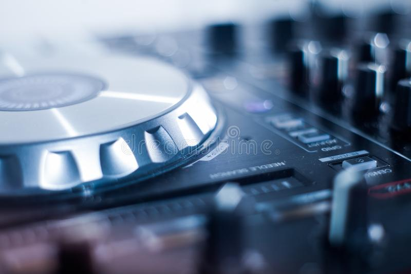 DJ playing music at mixer closeup and mixes the track in the nightclub royalty free stock image