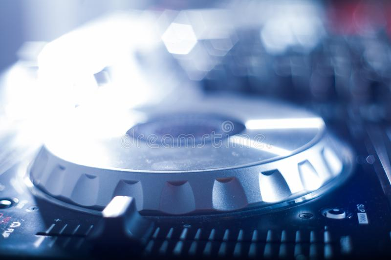 DJ playing music at mixer closeup and mixes the track in the nightclub royalty free stock images