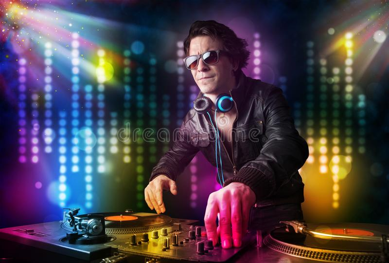 Dj playing songs in a disco with light show stock photo