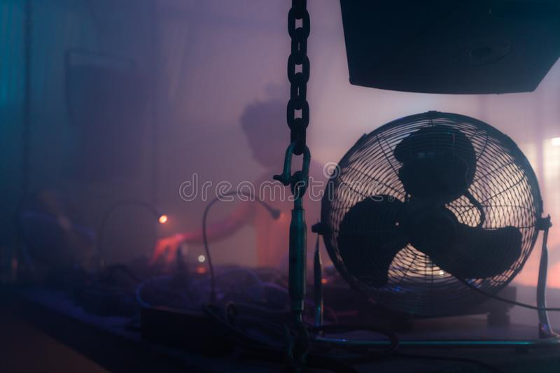 DJ playing vinyl records behind a turn table in a techno night club.  royalty free stock photography