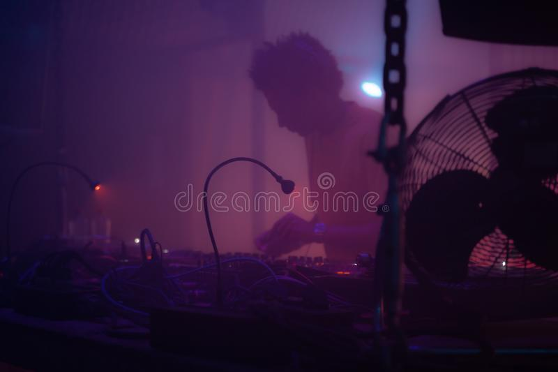 DJ playing vinyl records behind a turn table in a techno night club.  royalty free stock images
