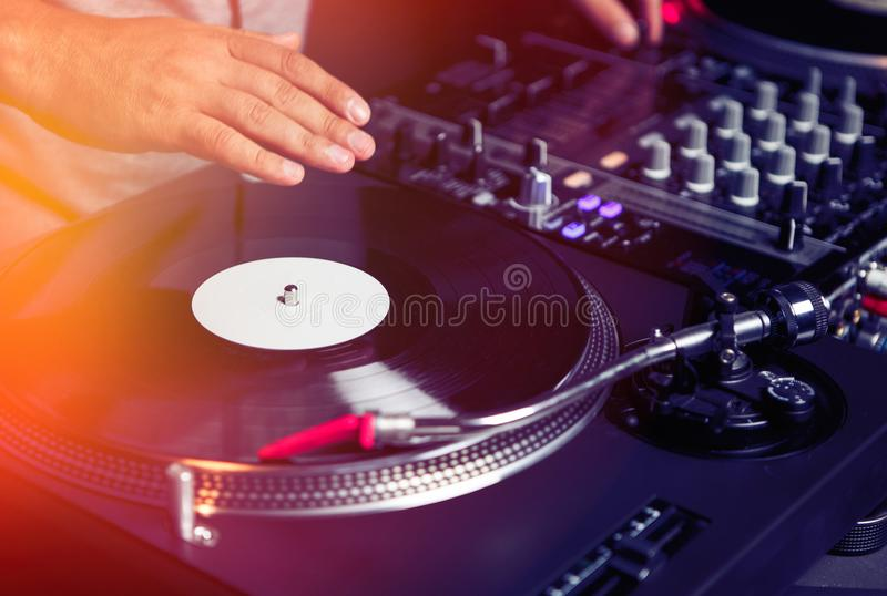 Dj plays music with retro turntables. Professional dj playing music with turntables and sound mixer.Stage audio equipment for nightclub party.Club disc jockey royalty free stock photography