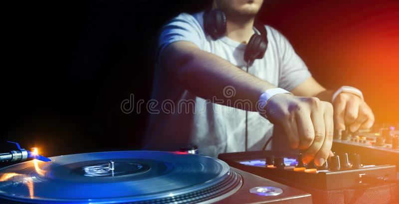 DJ plays set in vinyl player. Dj mixes the track in the nightclub at party. Vinyl Player in foreground royalty free stock photography