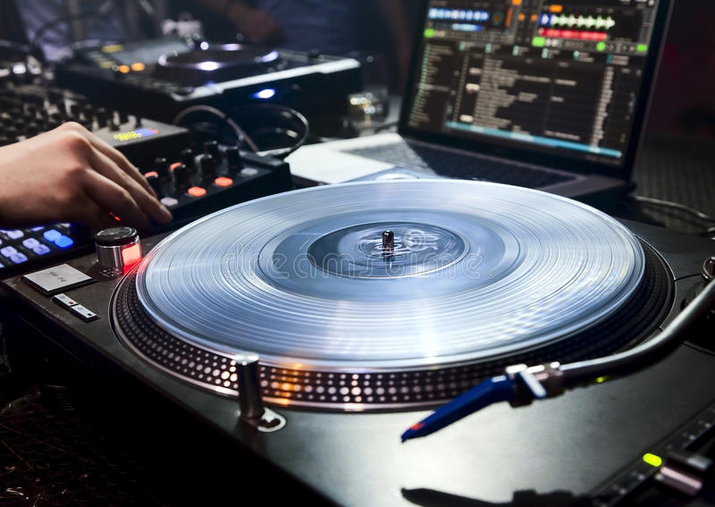 DJ plays set in vinyl player. Dj mixes the track in the nightclub at party. Vinyl Player in foreground royalty free stock photo