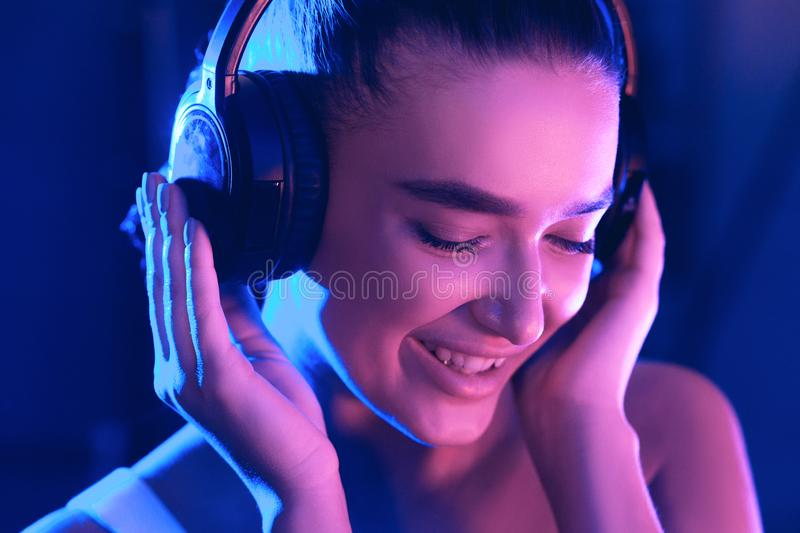 DJ portrait in blue and pink ligth, enjoying night party. And music in headset stock image