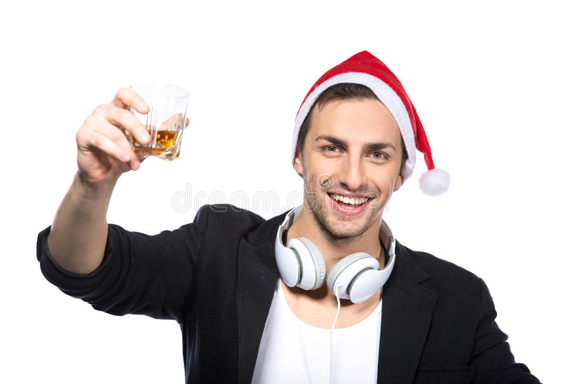 DJ. Portrait of young man with headphones and a glass of alcohol on the white background royalty free stock images