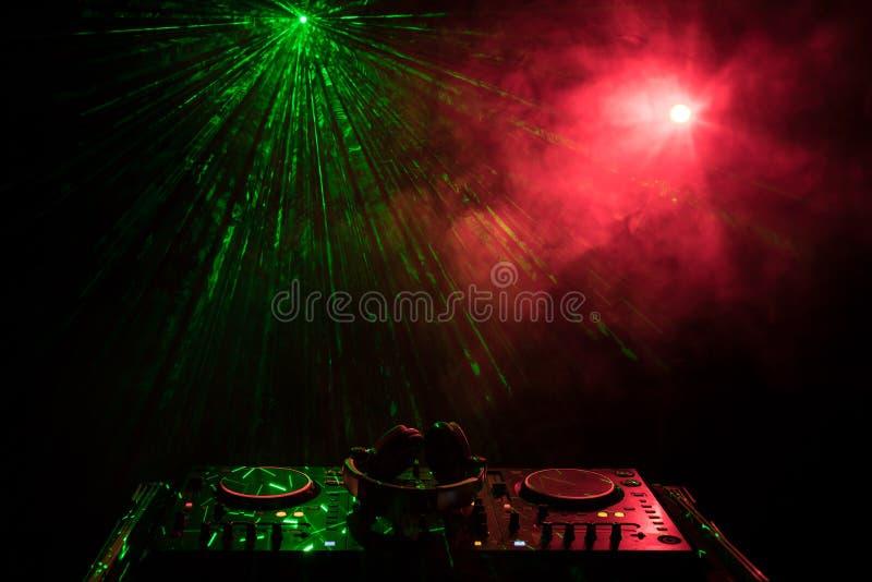 DJ que gira, misturando, e riscando em um clube noturno, nas mãos controles da trilha da emenda do DJ de vários na plataforma do  fotografia de stock