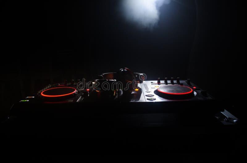 DJ que hace girar, mezclándose, y rasguñando en un club de noche, las manos de DJ pellizca diversos controles de la pista en la c imagen de archivo