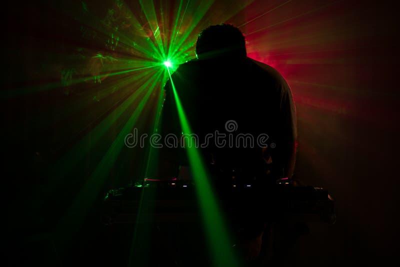 DJ que hace girar, mezclándose, y rasguñando en un club de noche, las manos de DJ pellizca diversos controles de la pista en la c foto de archivo