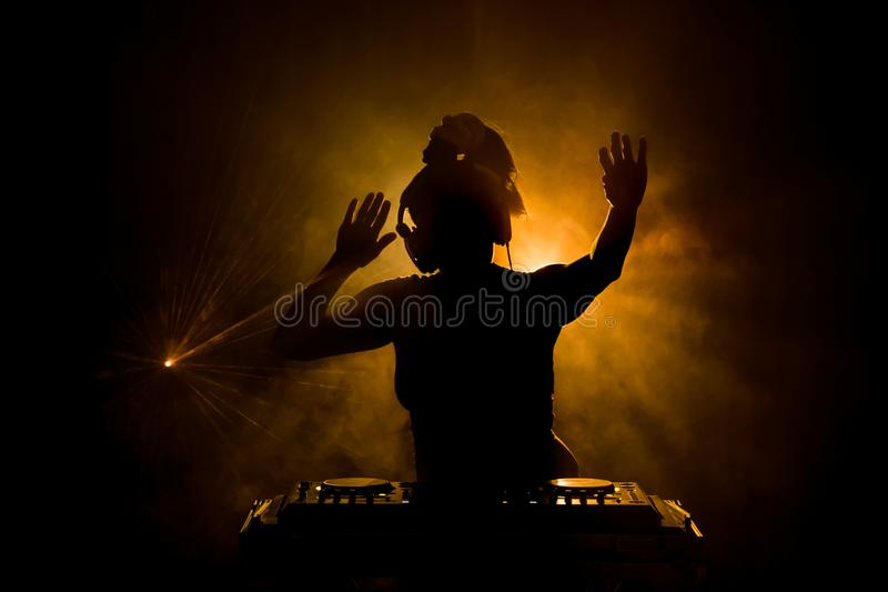 DJ que hace girar, mezclándose, y rasguñando en un club de noche, las manos de DJ pellizca diversos controles de la pista en la c imagen de archivo libre de regalías