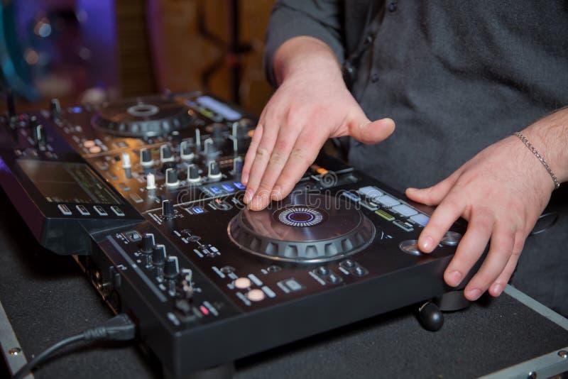 DJ que joga a música no close up do misturador Feche acima das mãos do DJ que misturam a música no festival eletrônico do partido fotos de stock
