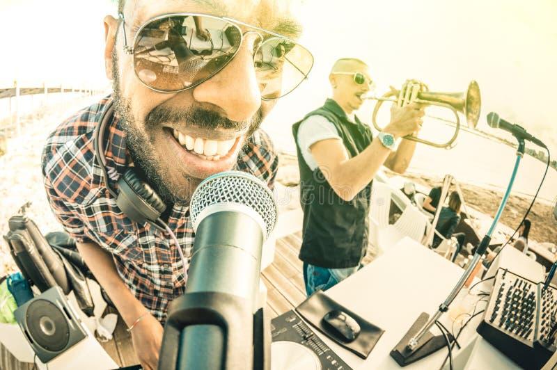 DJ que juega golpes del verano en el partido de la playa de la puesta del sol en evento de las vacaciones de primavera imagen de archivo libre de regalías