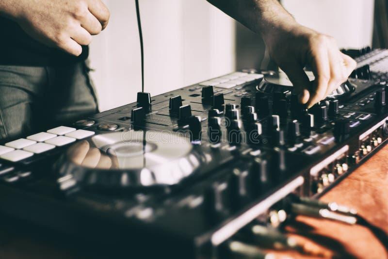 DJ que juega m?sica en el primer y las mezclas del mezclador la pista en el club nocturno fotografía de archivo