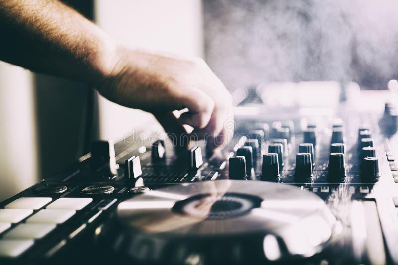 DJ que juega m?sica en el primer y las mezclas del mezclador la pista en el club nocturno fotografía de archivo libre de regalías