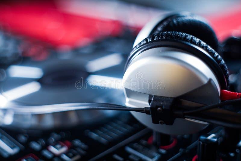 DJ que juega m?sica en el primer y las mezclas del mezclador la pista en el club nocturno imagen de archivo