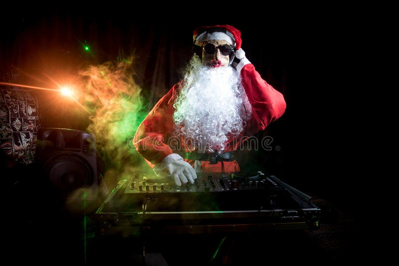 Dj Santa Claus at Christmas with glasses and snow mix on New Year's Eve event in the rays of light. Funny 2019 year of pig concept. Dj Santa with pig mask at royalty free stock images