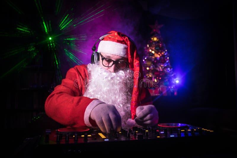 DJ Santa Claus no Natal com vidros e na mistura da neve no evento da véspera de Ano Novo nos raios de luz foto de stock