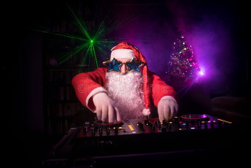 DJ Santa Claus no Natal com vidros e na mistura da neve no evento da véspera de Ano Novo nos raios de luz fotografia de stock royalty free