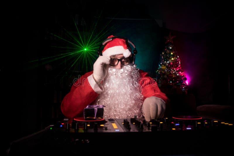 DJ Santa Claus no Natal com vidros e na mistura da neve no evento da véspera de Ano Novo nos raios de luz imagens de stock
