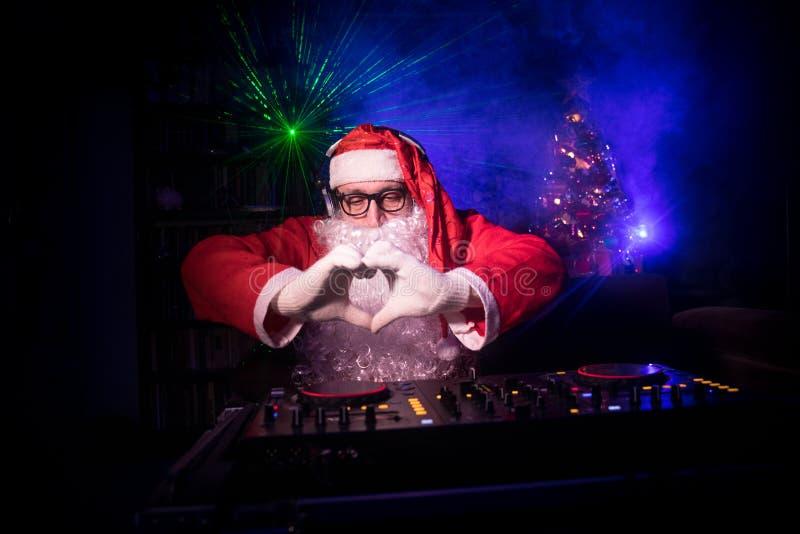 DJ Santa Claus no Natal com vidros e na mistura da neve no evento da véspera de Ano Novo nos raios de luz imagem de stock